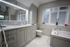 Painted shaker bespoke bathroom furniture with carrara marble surface.