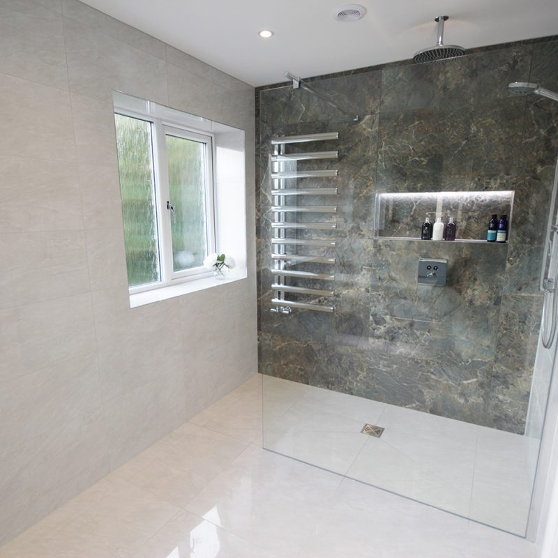 A stunning walk in shower with a feature wall tiled in Amazonite from Minoli.
